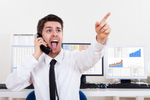 Enthusiastic young male stock broker in a bull market holding a telephone and yelling out a buy or sell order on stocks or bonds